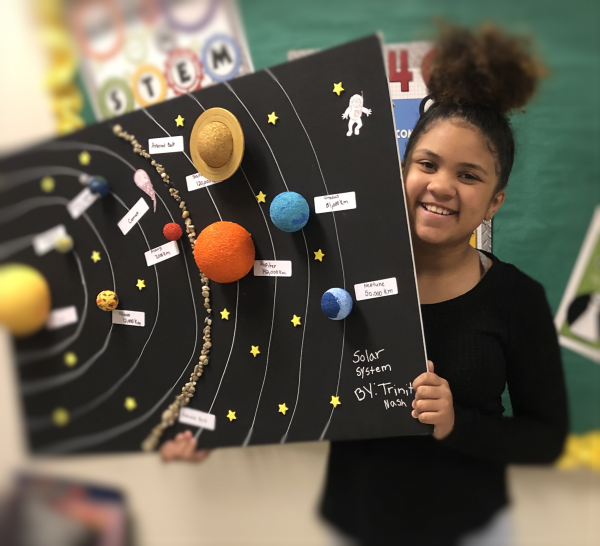 Student holding an excellent solar system project