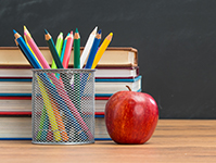 Apple, jar of pencils, stack of books