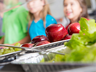 Closeup of apples and lettuce; children in lunch line