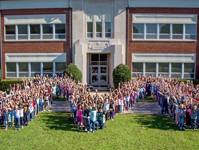 "Students and teacher form an ""M"" shape in front of the Midway school building"
