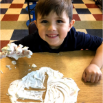 K student write letter F in cream with big smile